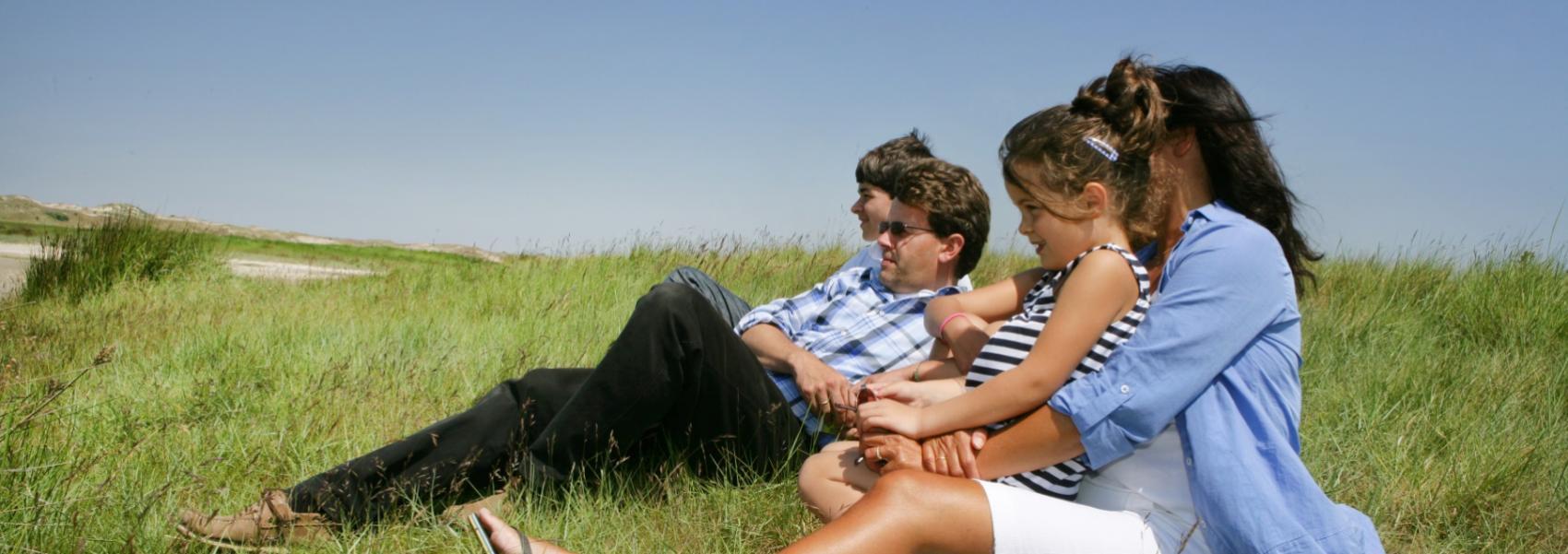 mensen in het gras uitkijkend over het landschap