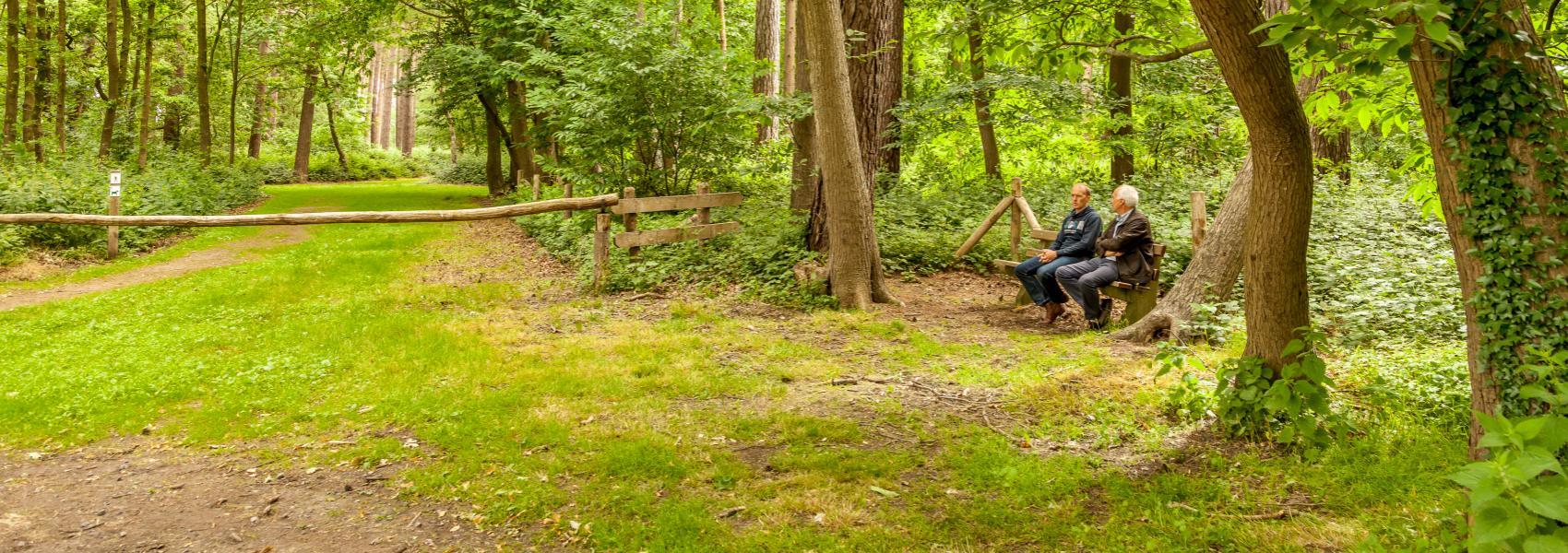 2 mannen op een bankje aan de ingang van het Koekelarebos