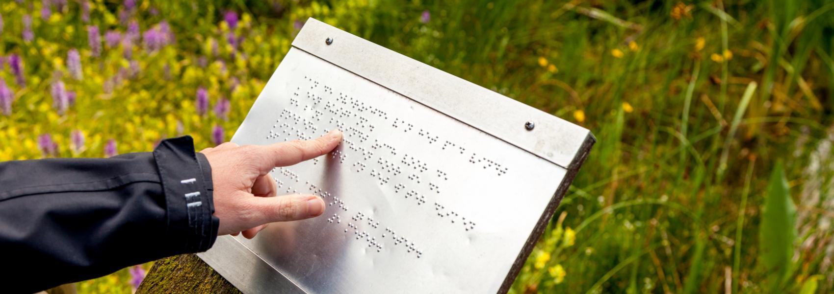 hand aan een bord voor blinden in de heemtuin