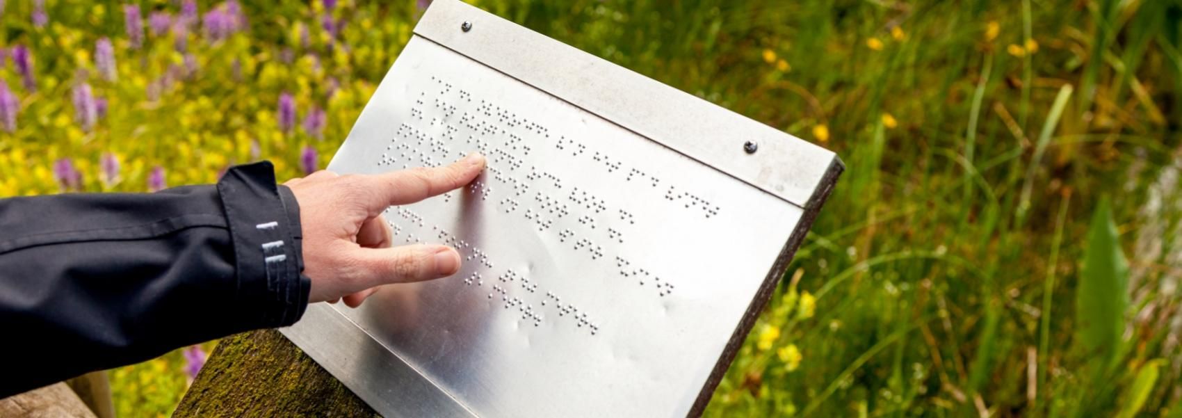 hand aan braillebord in de heemtuin