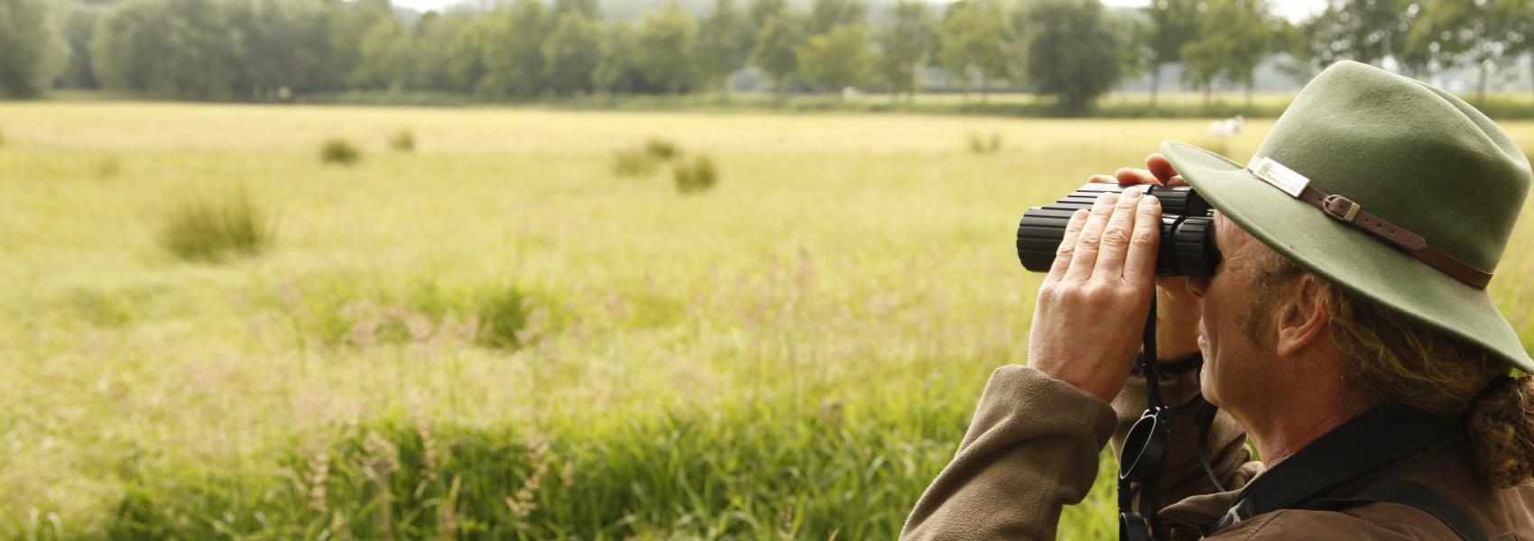 de boswachter bekijkt het landschap met zijn verrekijker