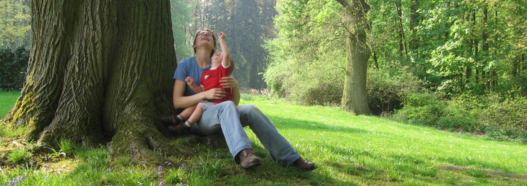 mama met kind die tegen een boom zitten