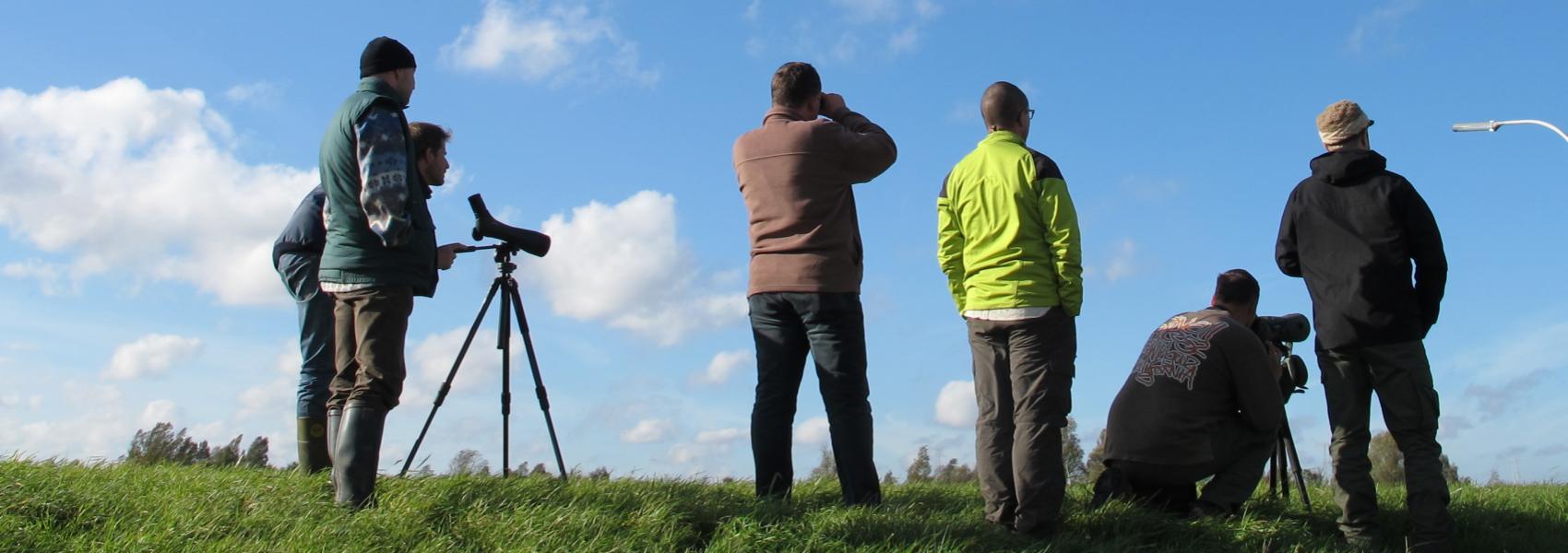 groep mannen die het landschap bestuderen met verrekijkers