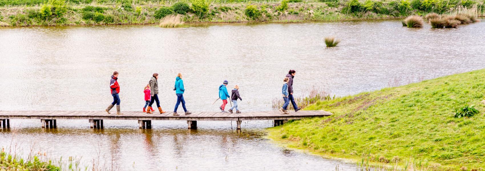 groep mensen wandelend op het vlonderpad