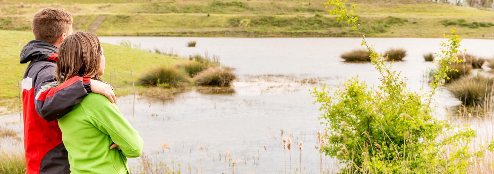 2 mensen turend over het water en landschap
