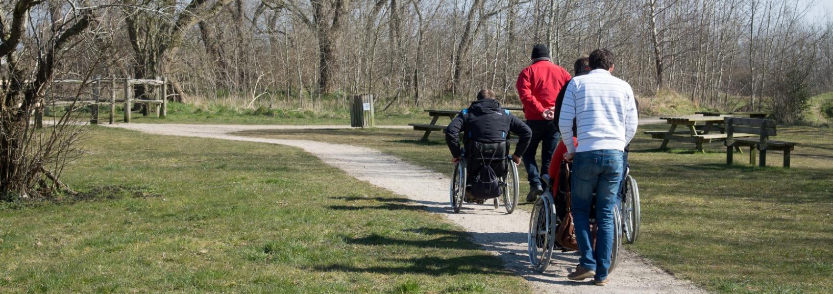 een klein groepje wandelaars met personen in een rolstoel