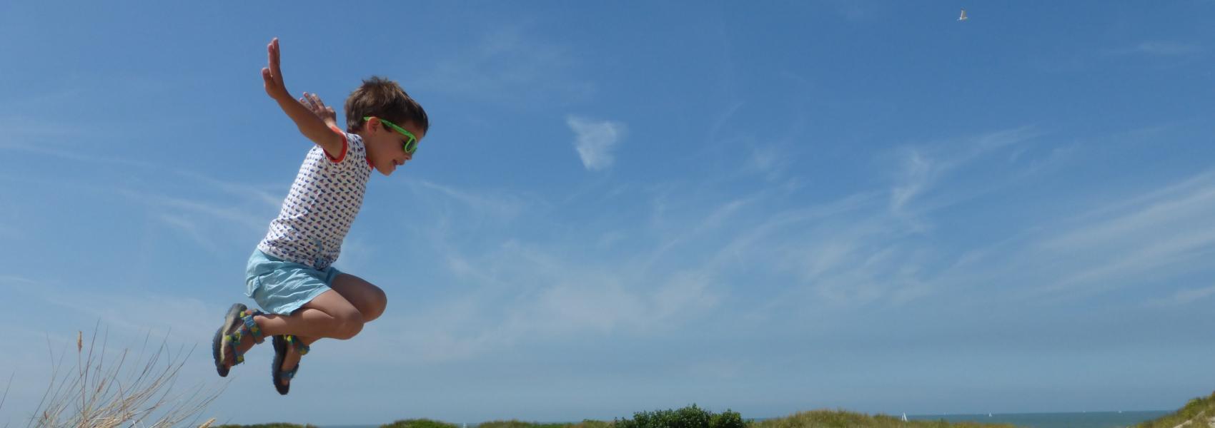 kind springt van zandheuvel