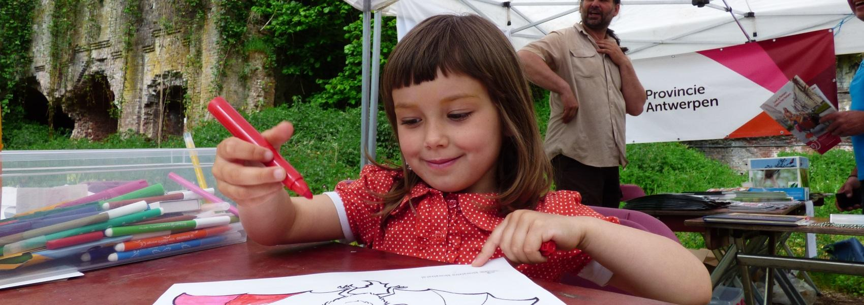 kind kleurt een tekening van een vleermuis