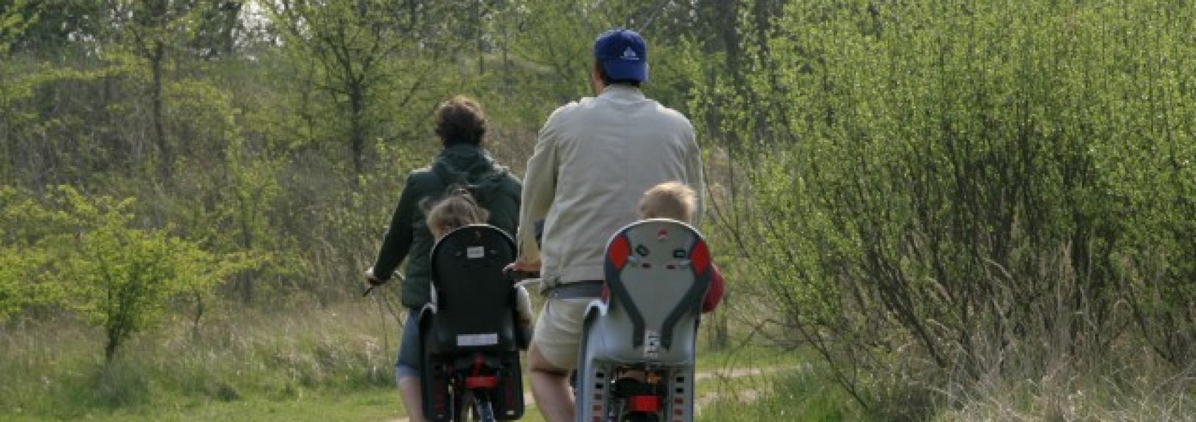 2 fietsers met kinderen achterop
