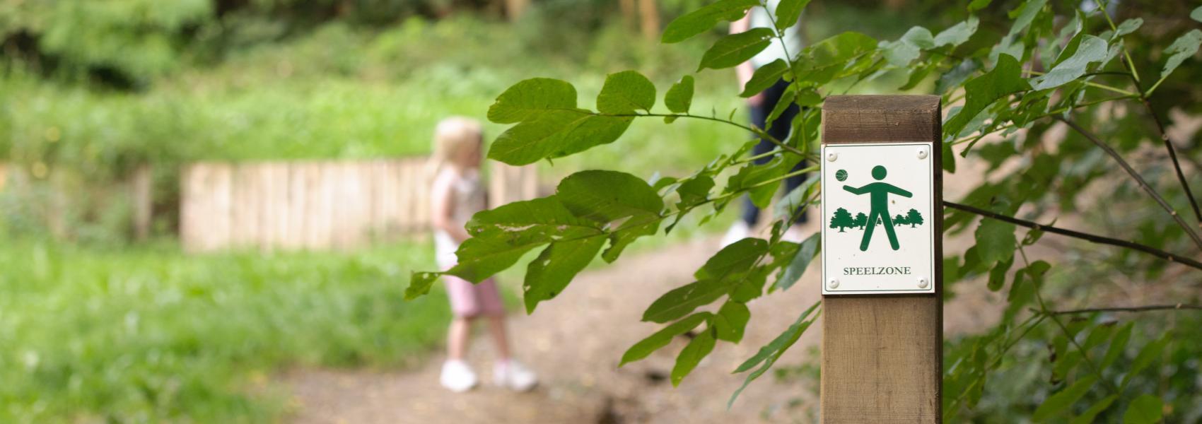 bordje speelzone met op de achtergrond mensen in het bos
