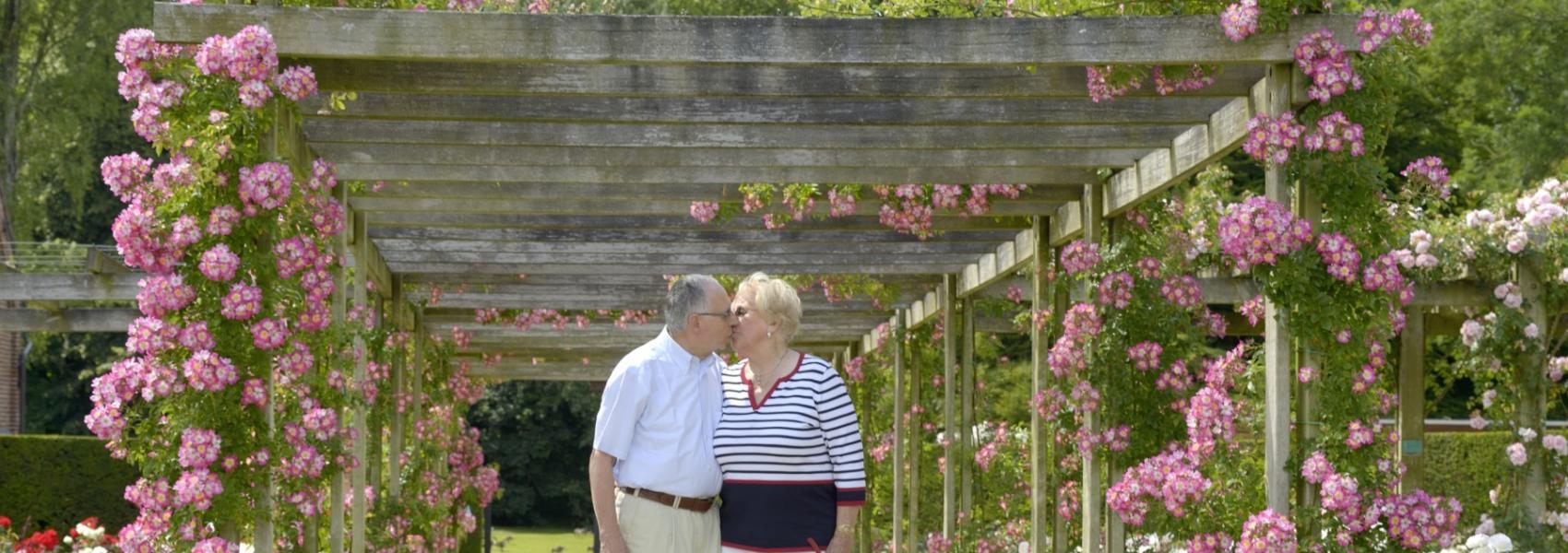 kussend koppel onder boog van rozen