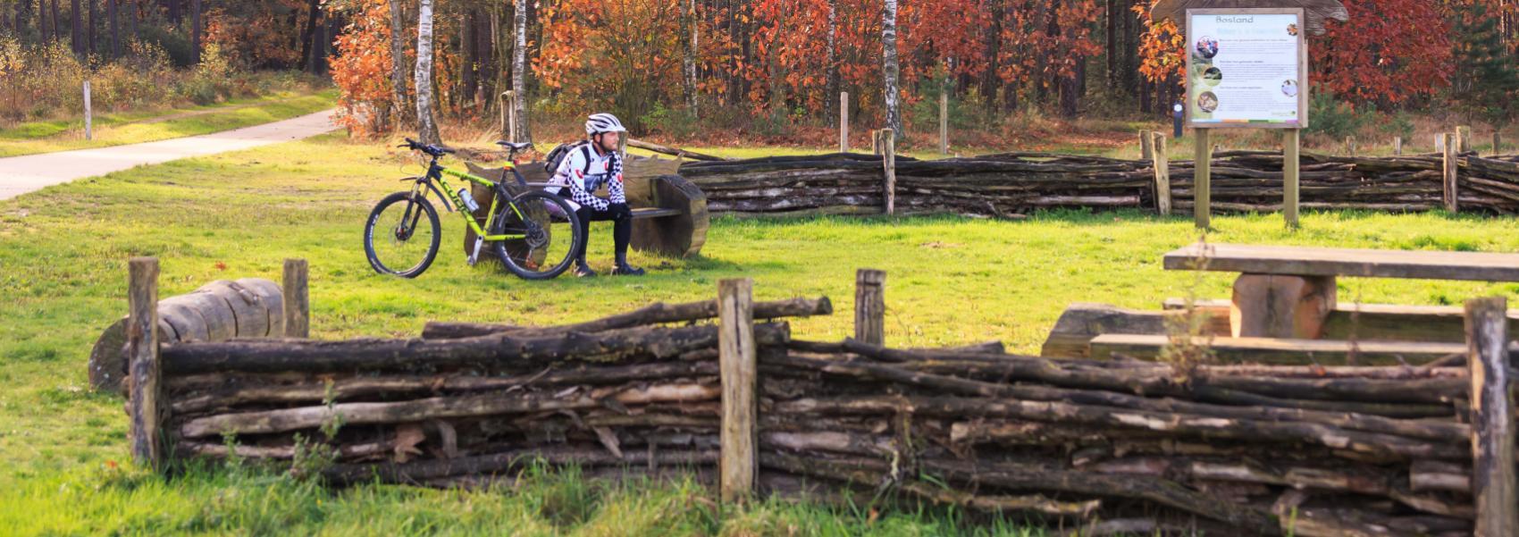 een fietser rust op een bankje in de vlindervallei
