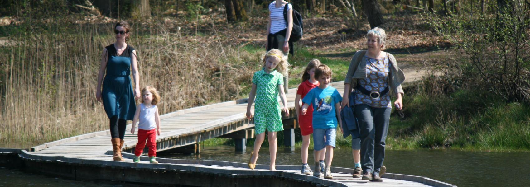 wandelaars op het vlonderpad over het water