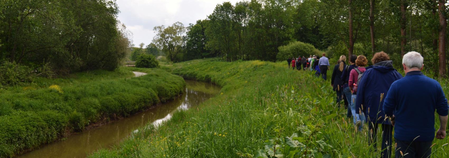 groep wandelaars op een rij langs een grasberm naast het water