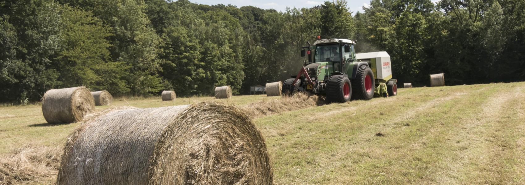traktor met op de voorgrond een ronde ballo hooi